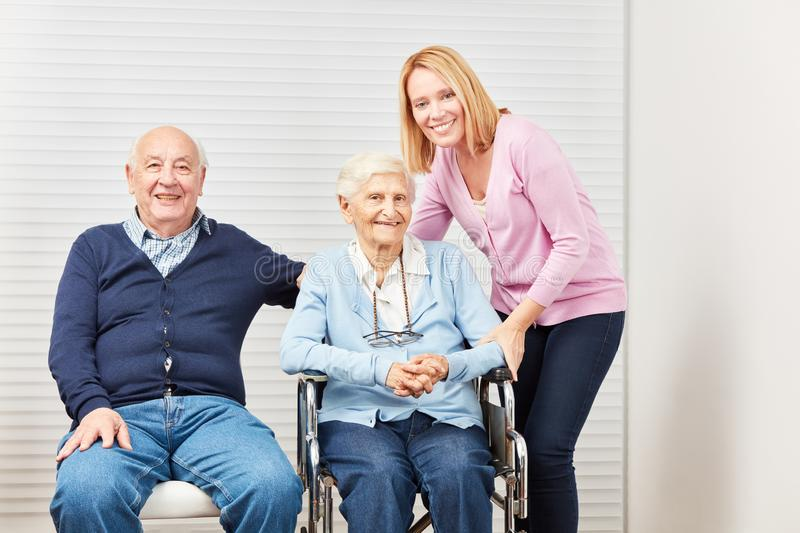 Senior couple and daughter at home care stock photography