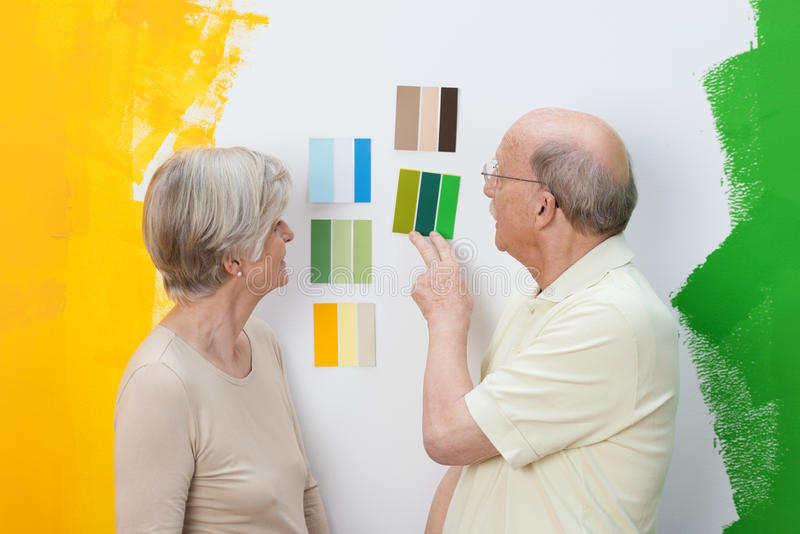 Senior couple deciding on a new paint colour royalty free stock photos