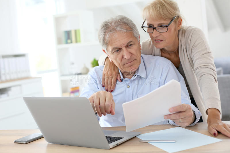 Senior couple doing administration paperwork together on laptop. Senior couple doing the income tax declaration online stock photo