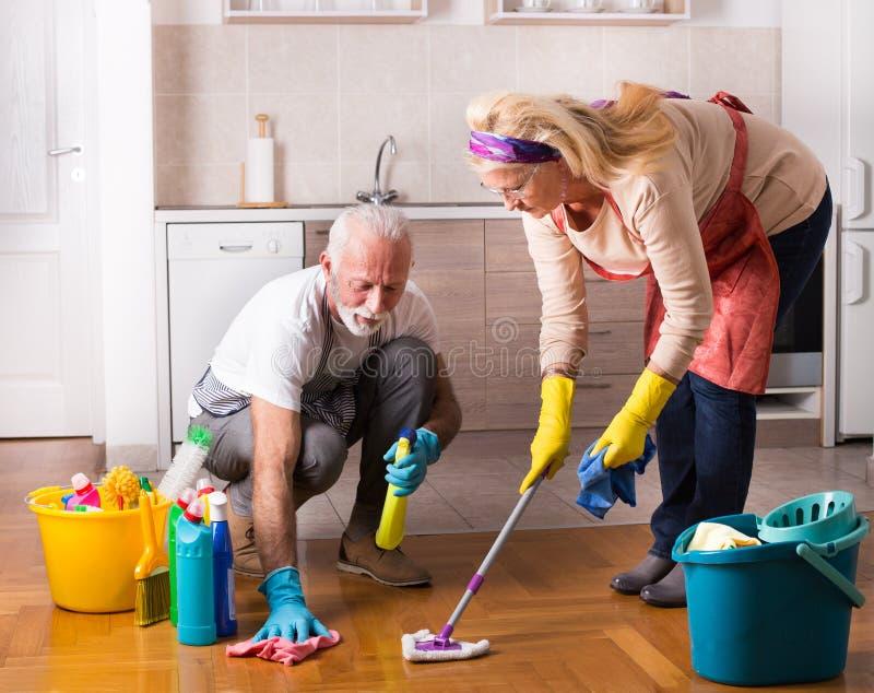 Senior couple doing chores. Happy senior couple doing chores together on floor royalty free stock photo