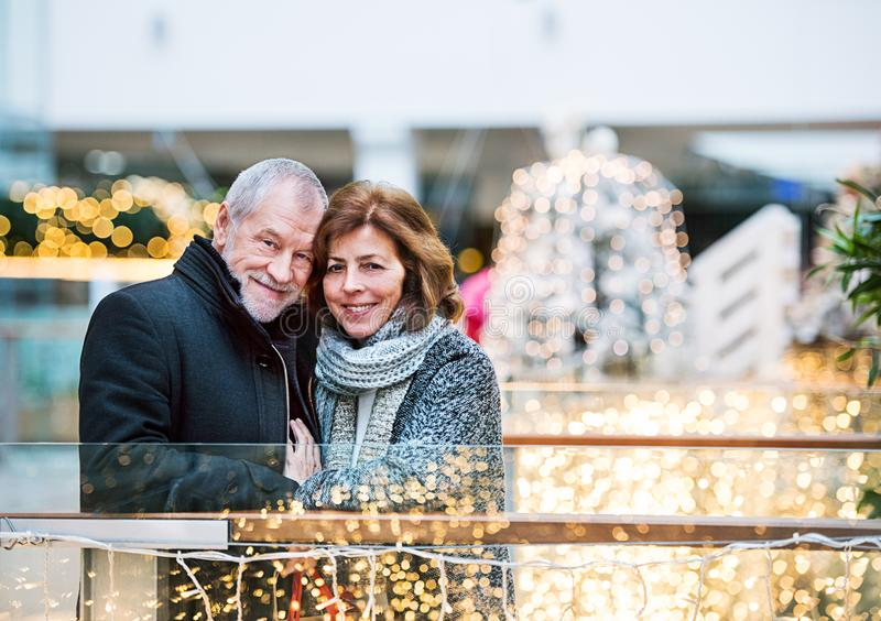 Happy senior couple doing Christmas shopping together. Senior couple doing Christmas shopping. Shopping center at Christmas time stock image