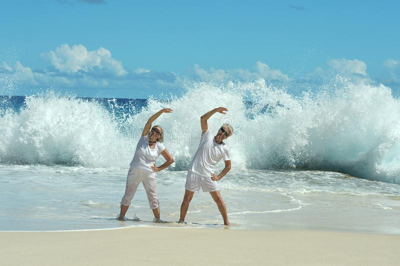 Senior couple doing exercises. On sandy beach stock photo