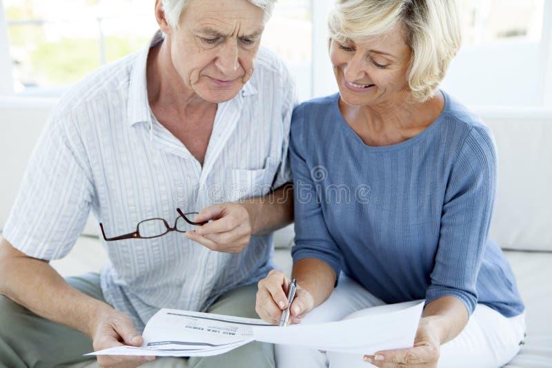 Senior couple doing home finance. Fake bill - women smiling stock photo
