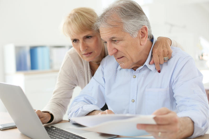 Senior couple doing paperwork at home. Senior couple doing the income tax declaration online stock photos