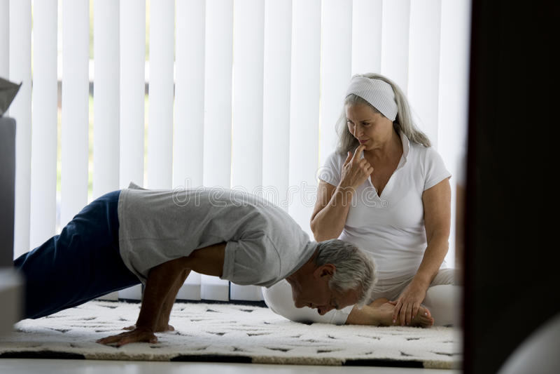 Senior couple doing yoga. Senior couple doing relaxing yoga in his home stock photos
