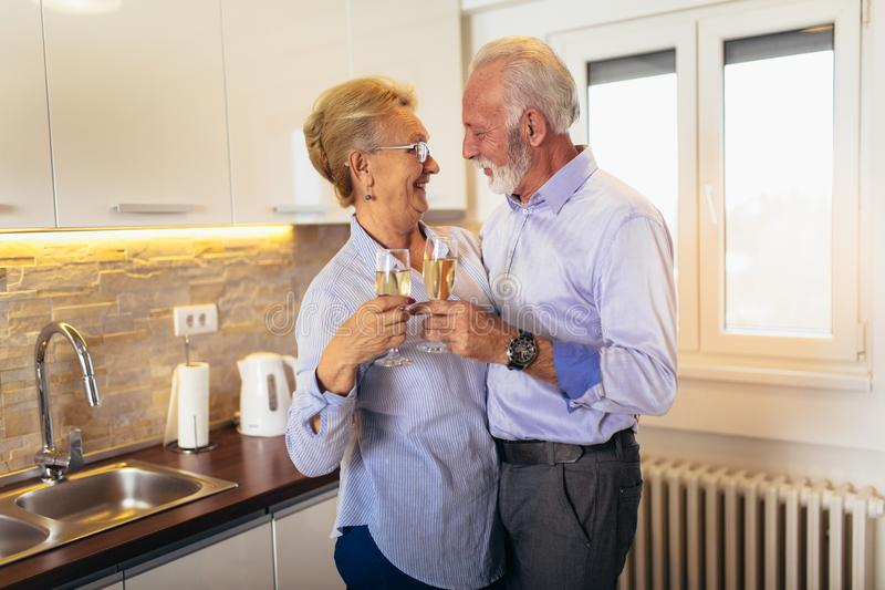 Senior couple drinking wine in kitchen stock images