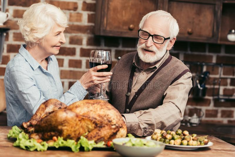senior couple drinking wine on thanksgiving dinner with turkey royalty free stock photo