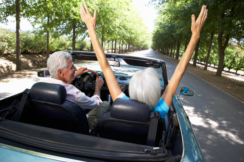 Senior couple driving in sports car royalty free stock images