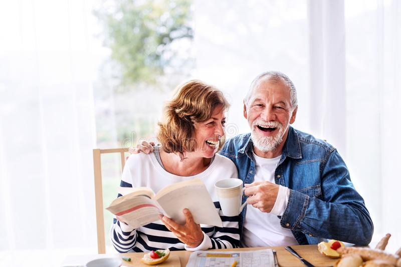 Senior couple eating breakfast at home. stock photos