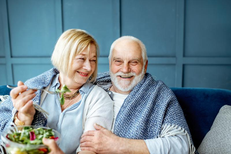 Senior couple eating healthy salad on the couch at home royalty free stock photo