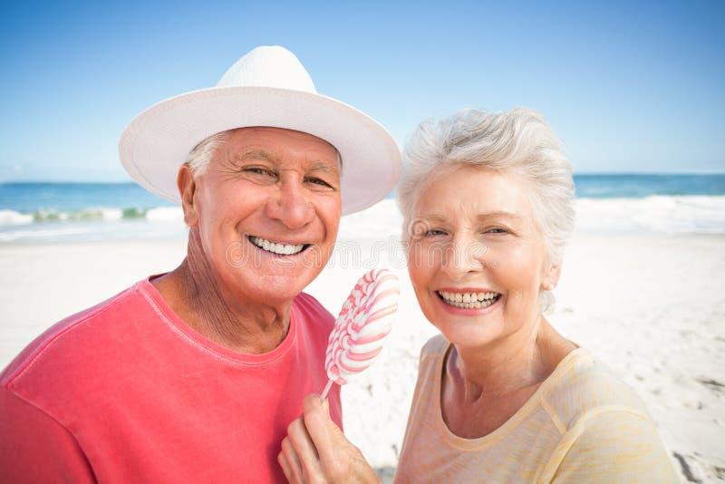 Senior couple eating lollipop royalty free stock photo