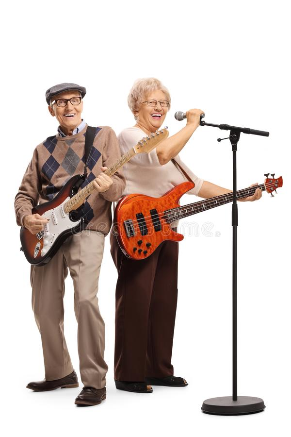 Senior couple with electric guitars singing on a microphone royalty free stock photos