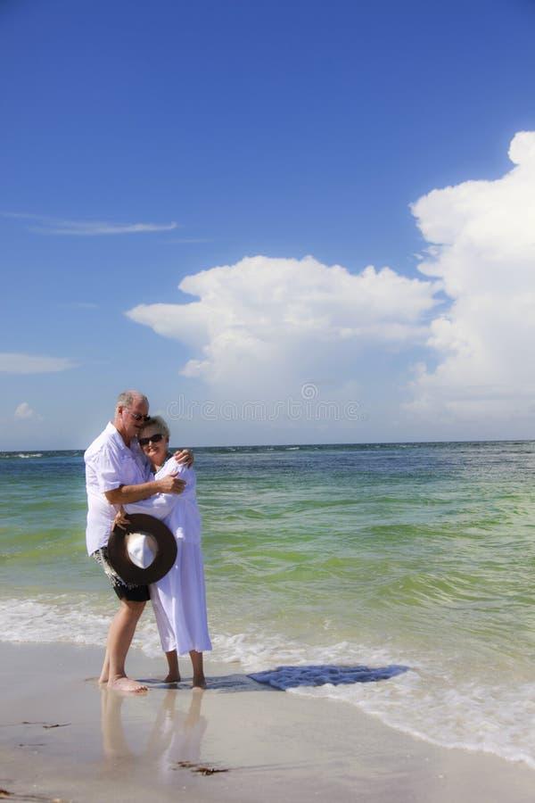 Senior couple embrace on beach. A mature couple hugging on a tropical beach