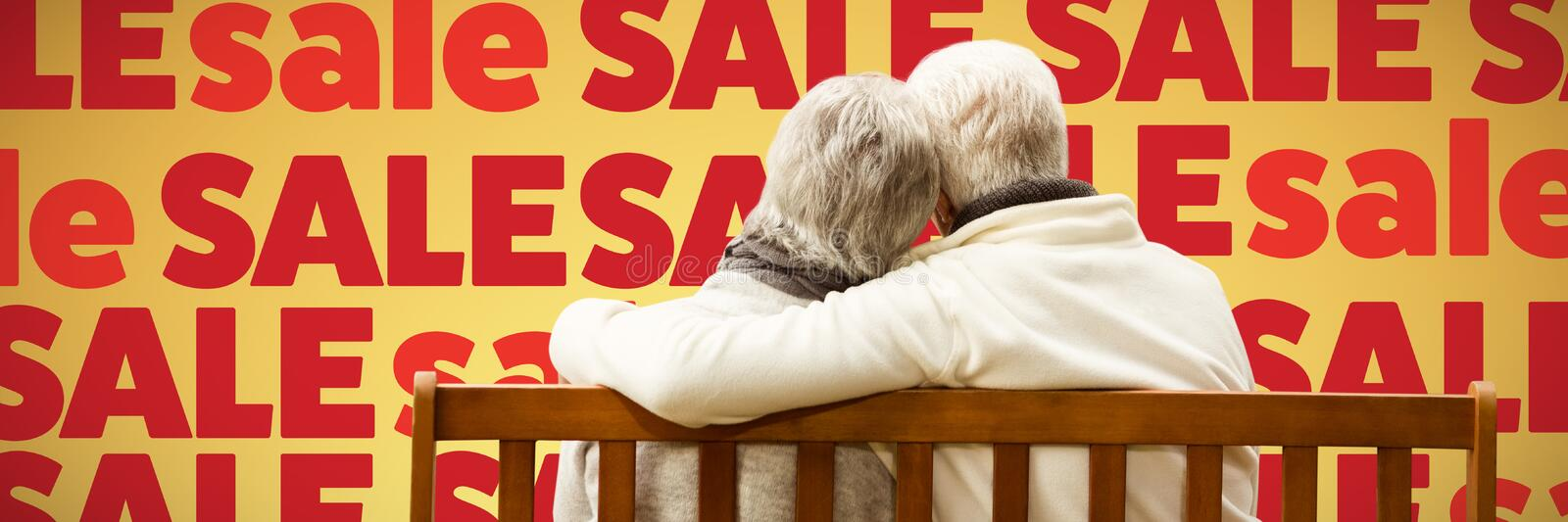 Composite image of senior couple embracing on a bench royalty free stock photo
