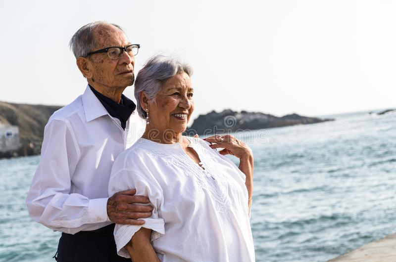 Senior couple embracing each other on the beach. stock image