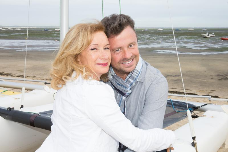 Senior couple embracing in front of beach with boat stock photo