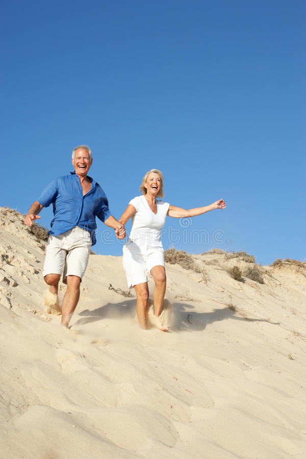 Senior Couple Enjoying Beach Holiday Running Stock Image