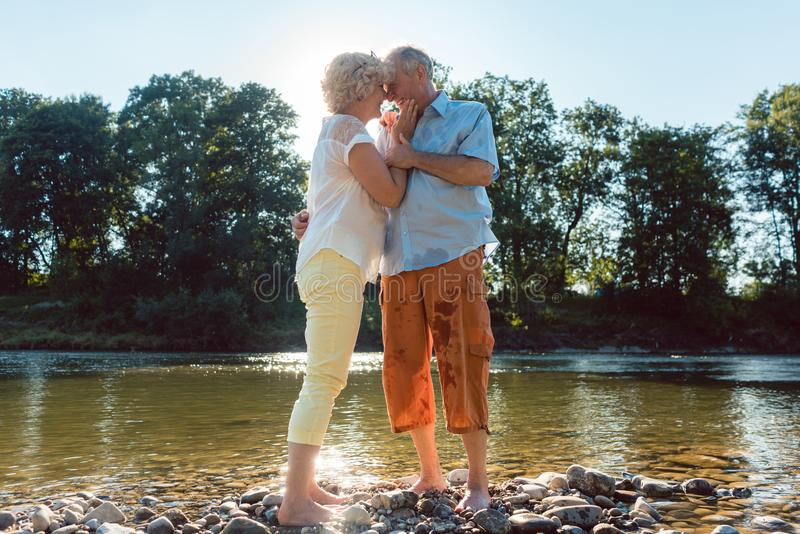 Senior couple enjoying a healthy and active lifestyle outdoors in summer. Low-angle side view portrait of a romantic senior couple in love enjoying a healthy and stock photo
