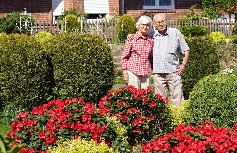 Senior couple enjoying her garden stock photography