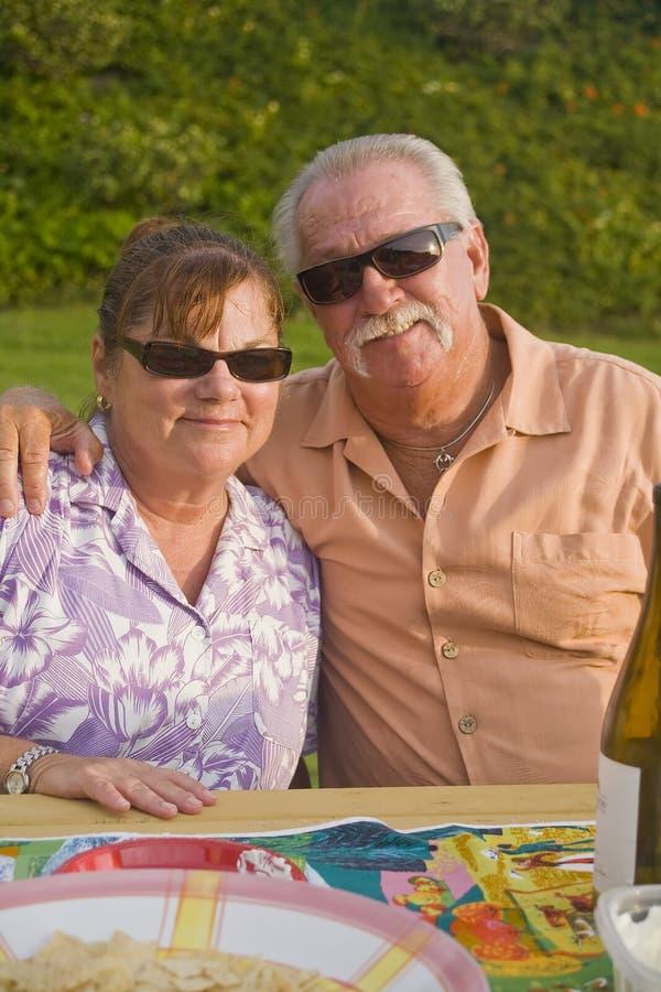 Senior Couple enjoys a Picnic Vertical Orientation. Senior Couple enjoys a Picnic outdoors Vertical Orientation royalty free stock photography