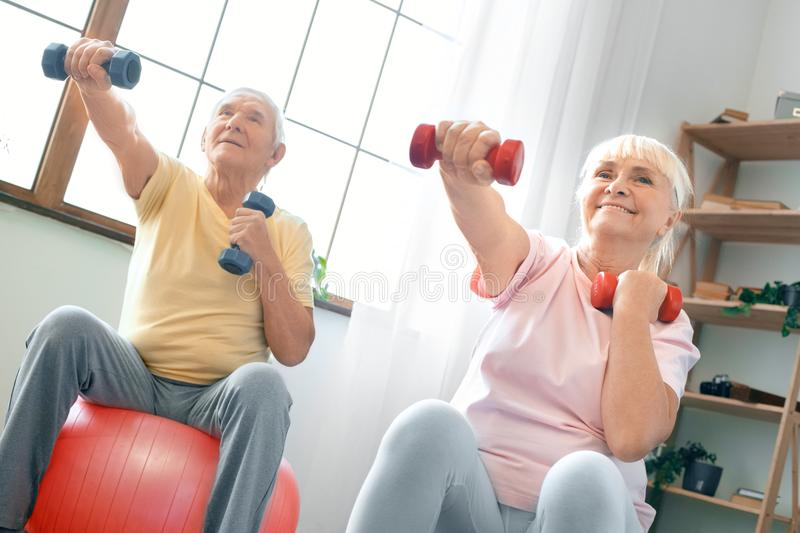 Senior couple exercise together at home doing aerobics with dubbells in front. Senior men and women together indoors sitting on exercise ball doing aerobics with stock photo