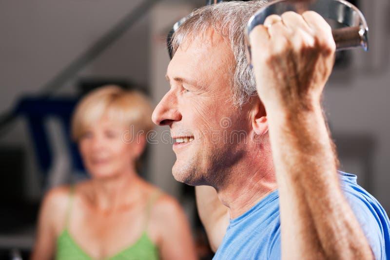 Senior couple exercising in gym stock photo