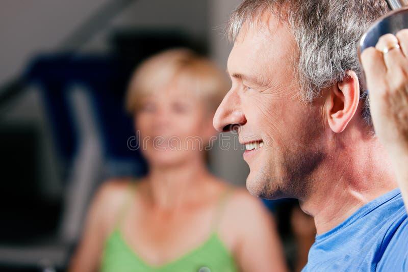 Senior Couple Exercising In Gym Stock Photography