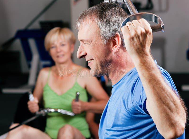 Senior couple exercising in gym royalty free stock photos