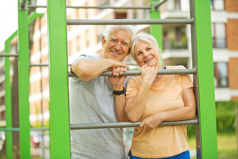 Senior couple exercising at outdoor gym. Smiling happy elderly seniors couple royalty free stock image
