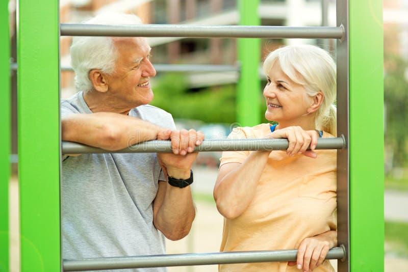 Senior couple exercising at outdoor gym. Smiling happy elderly seniors couple stock image