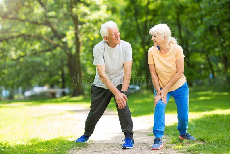 Senior Couple Exercising In Park. Smiling happy elderly seniors couple stock photos