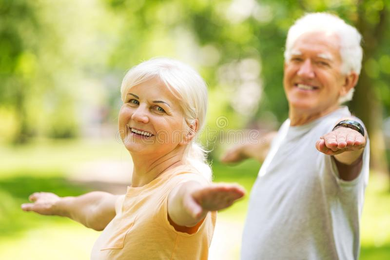Senior Couple Exercising In Park. Smiling happy elderly seniors couple royalty free stock images