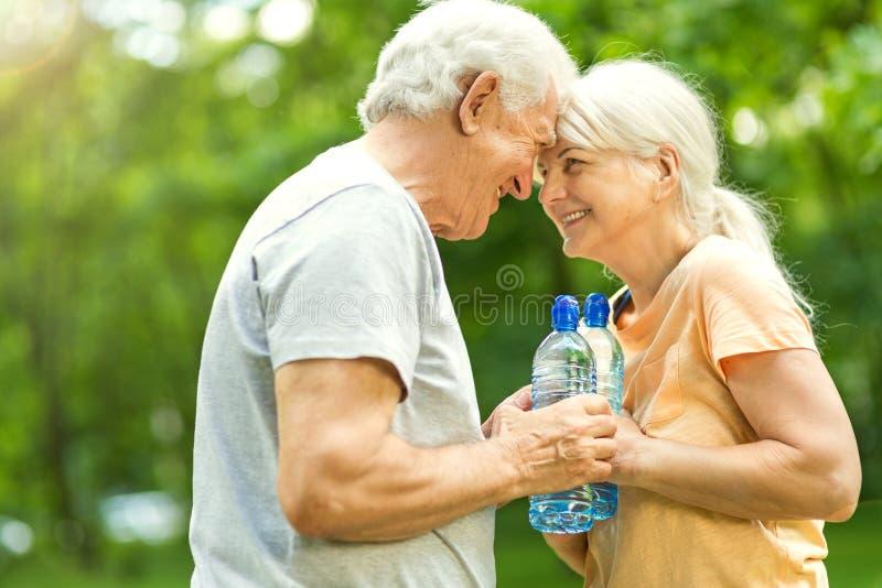Senior Couple Exercising In Park. Smiling happy elderly seniors couple stock photography
