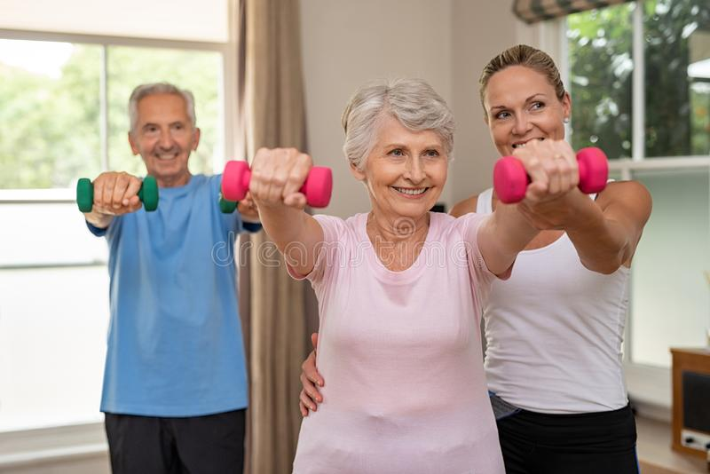 Senior couple exercising using dumbbells royalty free stock image