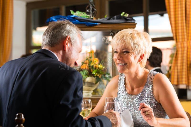 Senior couple fine dining in restaurant. Senior couple fine dining food at table in hotel or elegant restaurant stock photo