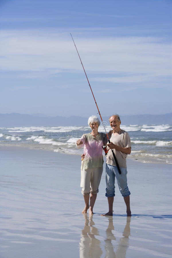 Senior couple with fishing rod on beach, smiling, portrait royalty free stock photography