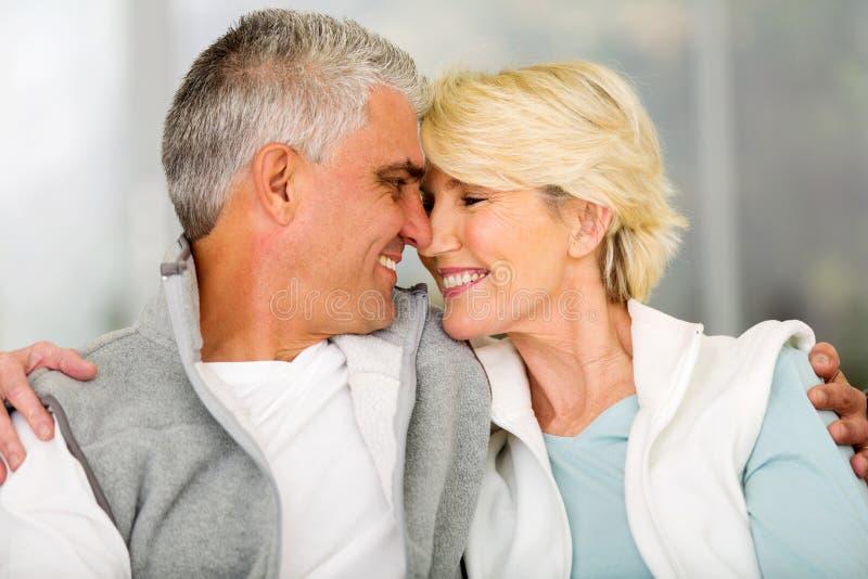 Senior couple flirting. Lovely senior couple flirting at home stock images
