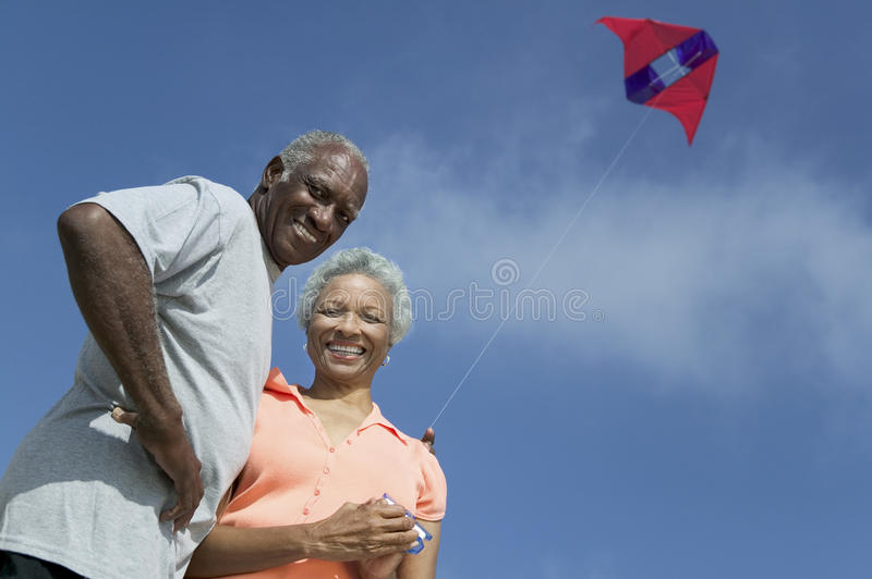 Senior couple flying kite outdoors (low angle view) (portrait) royalty free stock photos