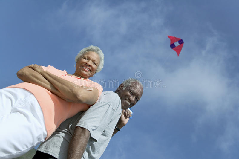 Senior couple flying kite outdoors (low angle view) (portrait) stock photos