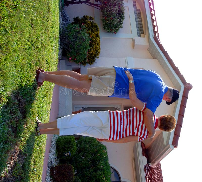 Senior couple in front of home. A rear view of a senior couple standing with arms around one another in front of a house
