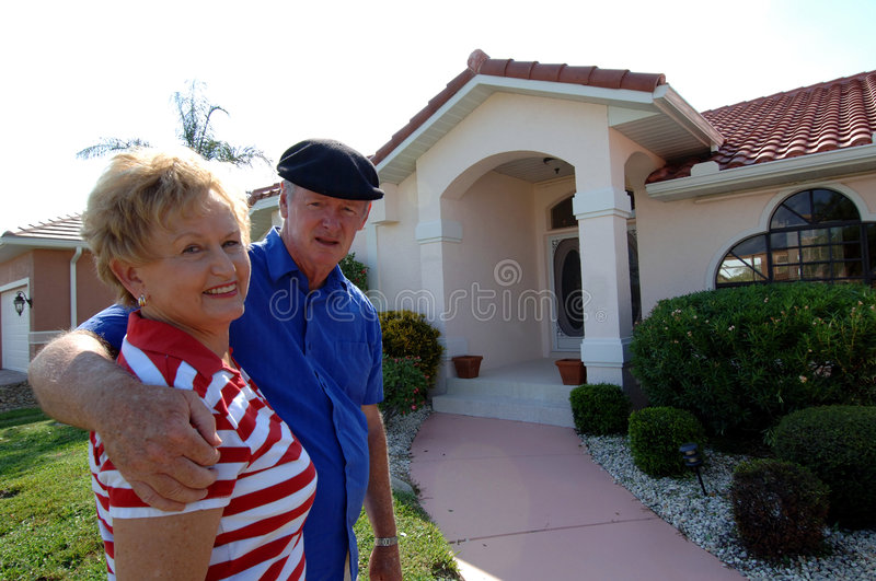 Senior couple in front of home. A senior couple with arms around each other in front of a single family house