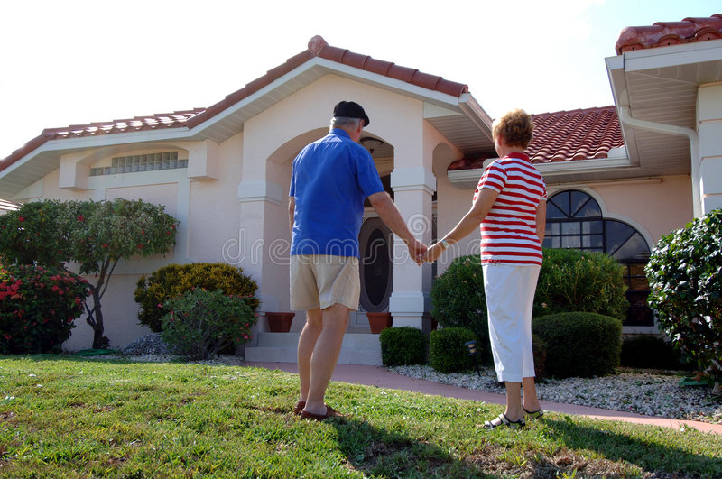 Senior couple in front of home. A rear view of a senior couple holding hands in front of a house
