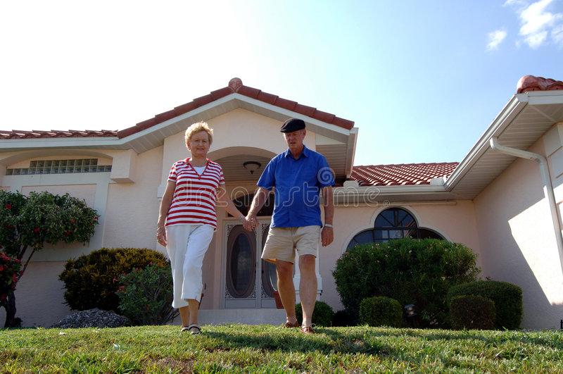 Senior couple in front of home. A senior couple walking in front of a single family house
