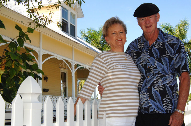 Senior couple in front of house. A happy senior couple standing in front of white picket fence and Victorian home