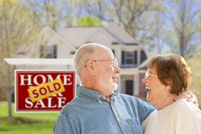 Senior Couple in Front of Sold Real Estate Sign and House. Happy Affectionate Senior Couple Hugging in Front of Sold Real Estate Sign and House stock photo