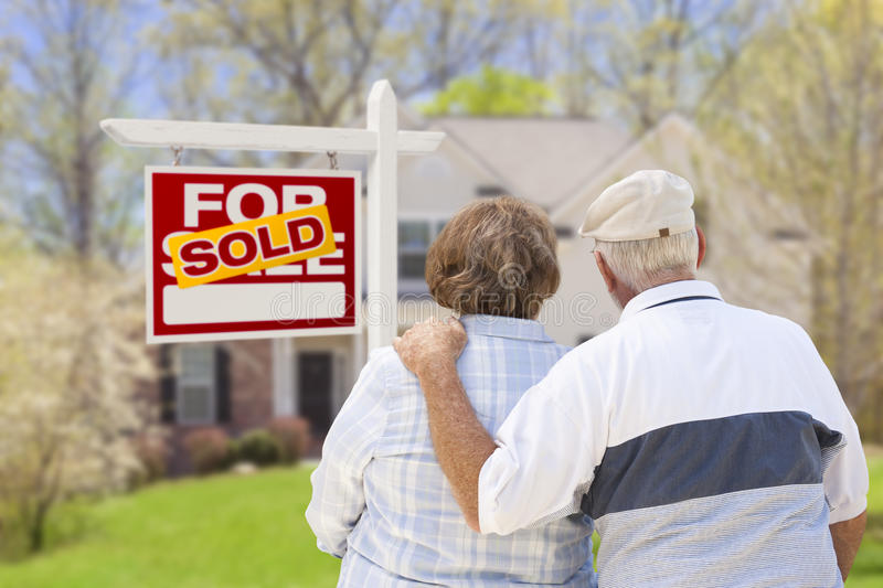 Senior Couple in Front of Sold Real Estate Sign and House. Happy Affectionate Senior Couple Hugging in Front of Sold Real Estate Sign and House stock images