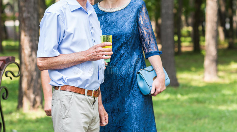 Senior couple with glass of champagne outdoors stock photo