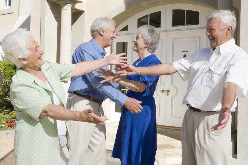 Senior couple greeting friends stock photo