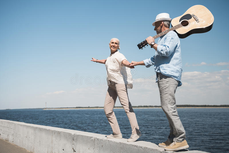 Senior couple with guitar holding hands and walking at quay. Happy senior couple with guitar holding hands and walking at quay royalty free stock photos