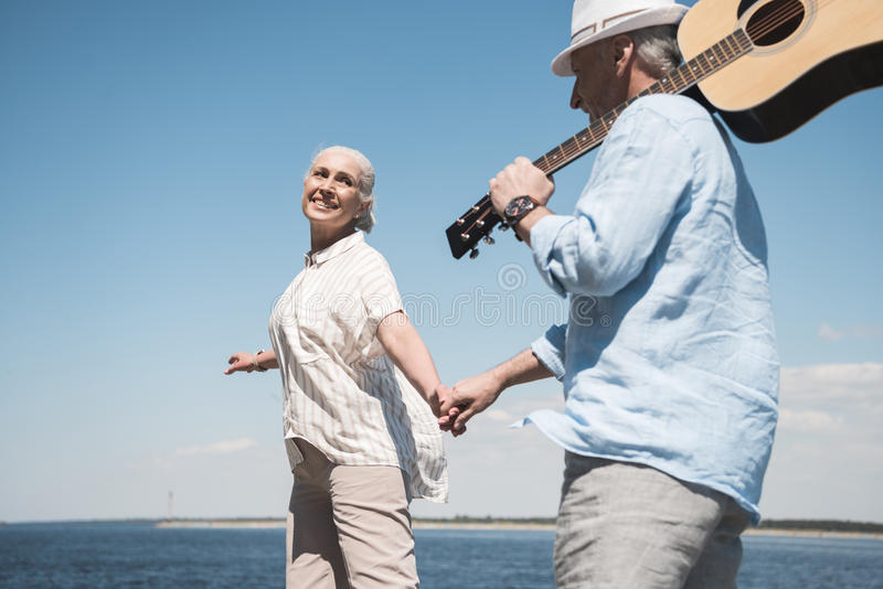 Senior couple with guitar holding hands and walking at quay. Happy senior couple with guitar holding hands and walking at quay stock image